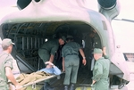 Loading patient into Chinook for transport by Cayetano E. Barrera
