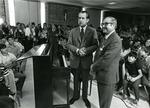 Photograph of President Richard Nixon in standing front of a piano beside Kika de la Garza