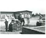 Photograph of Kika de la Garza viewing the laying of adobe bricks for a building