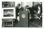 Photograph of Kika de la Garza speaking at a press conference beside a painting of the Santa Maria ship